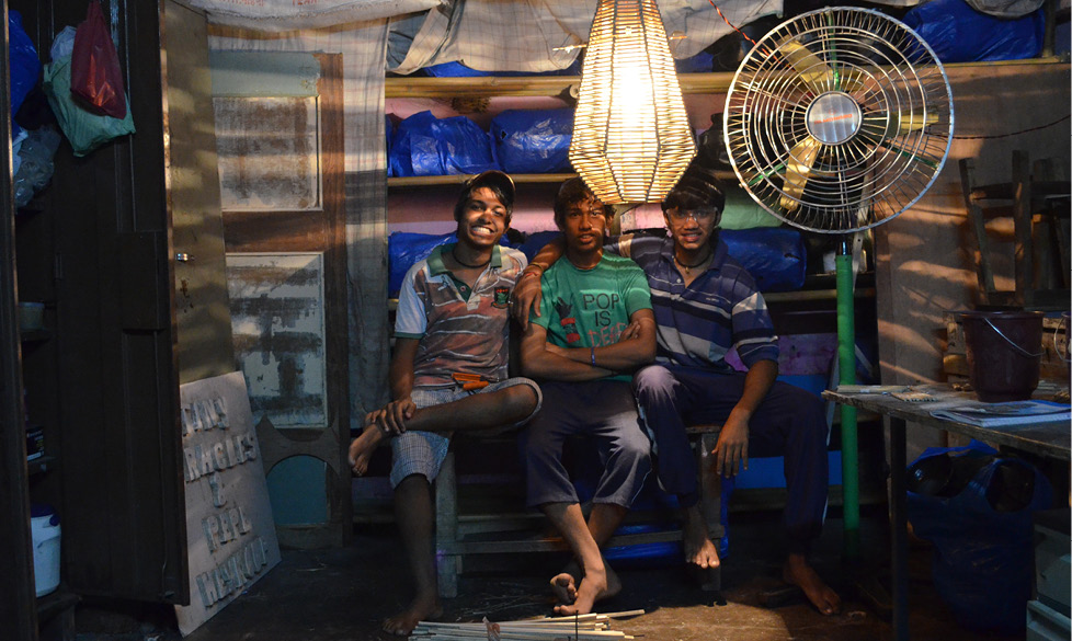 3 young men looking at camera with bamboo lamp