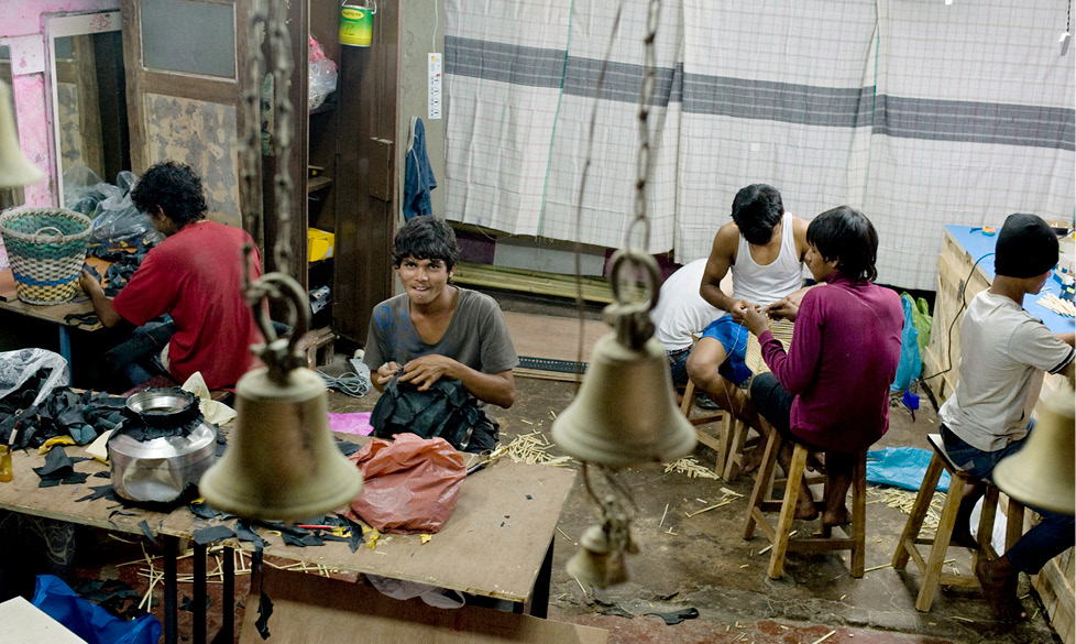 men inside workshop working in the bamboo lamps