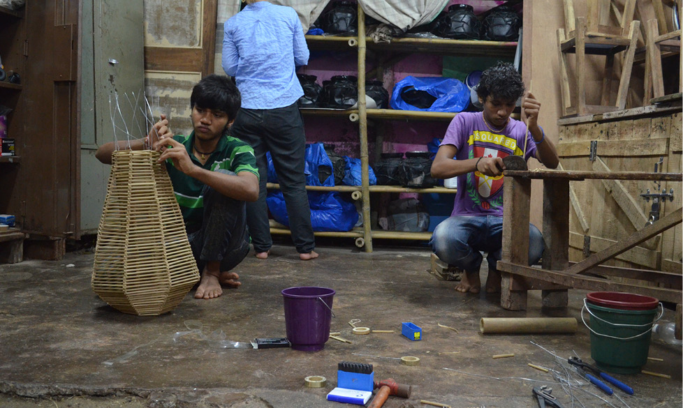 young men working on making bamboo lamps in the slums of Mumbai